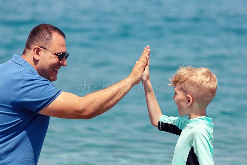 Rozochocona chłopiec w surfingu swimwear daje wysokości pięć tata na plażowym wyraża zaufaniu i zaufaniu obrazy royalty free