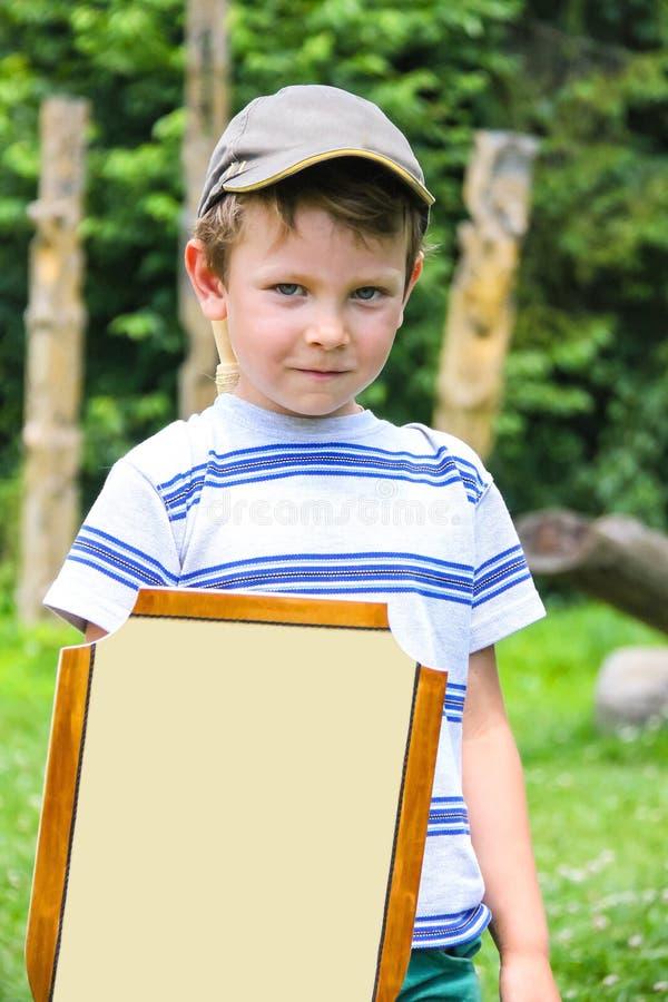 Rozochocona chłopiec z drewnianym kordzikiem i osłoną zdjęcie stock