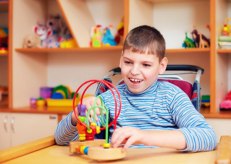 Rozochocona chłopiec z kalectwem przy centrum rehabilitacji dla dzieciaków z dodatek specjalny potrzebami, rozwiązuje logiczną ła fotografia stock