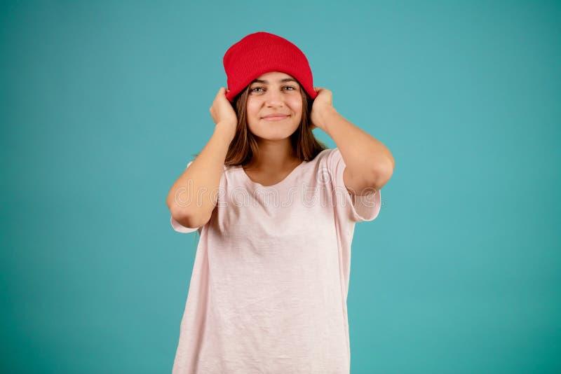 Rozochocona dziewczyna jest ubranym czerwoną nakrętkę i białą koszulkę zdjęcie stock