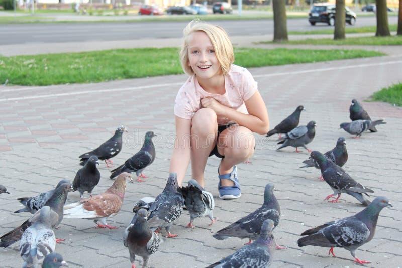 Rozochocona dziewczyna karmi gołębie na ulicie w mieście obrazy stock