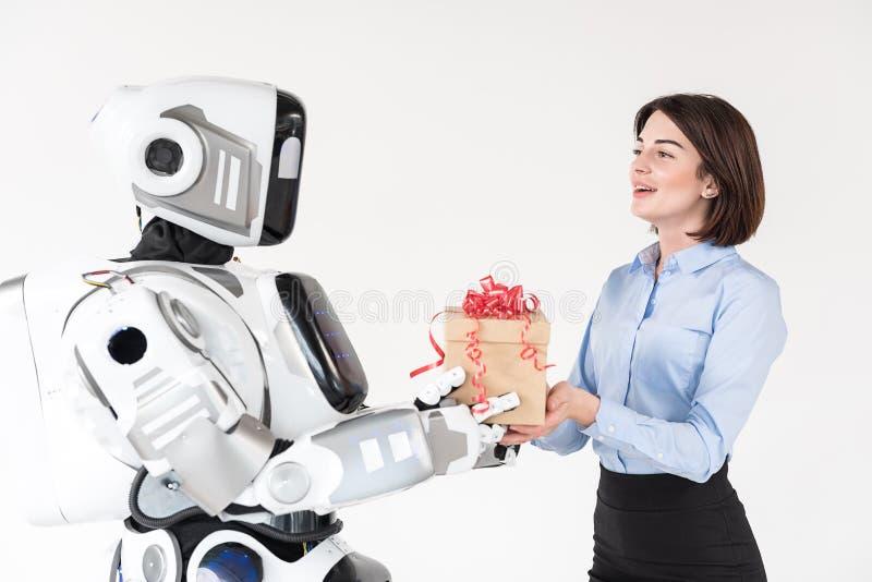 Rozochocona dziewczyna otrzymywa teraźniejszość od chłopaka robota zdjęcie royalty free