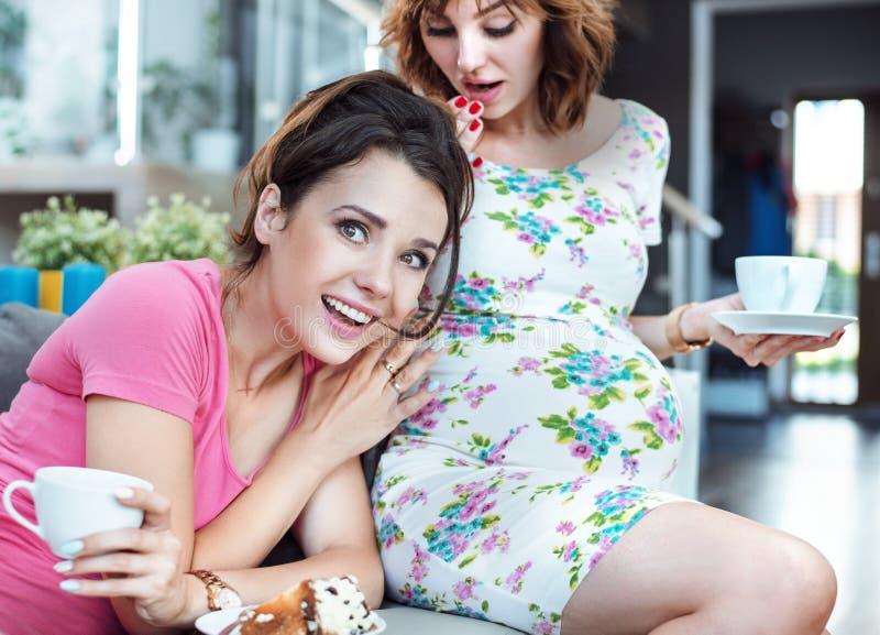 Rozochocona dziewczyna słucha ciężarny ` s przyjaciela brzuch zdjęcia stock