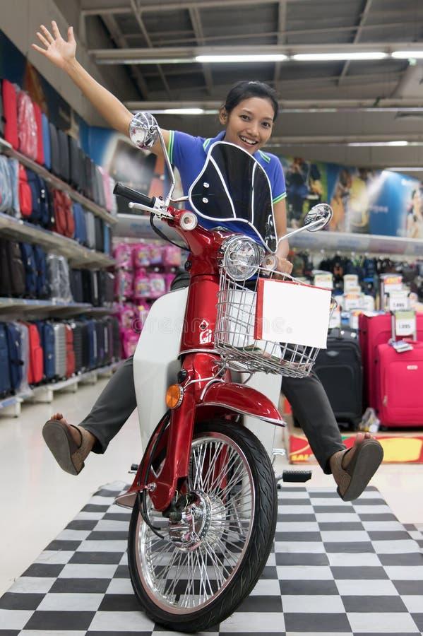 Rozochocona dziewczyna siedzi na motocyklu w centrum handlowym obrazy royalty free