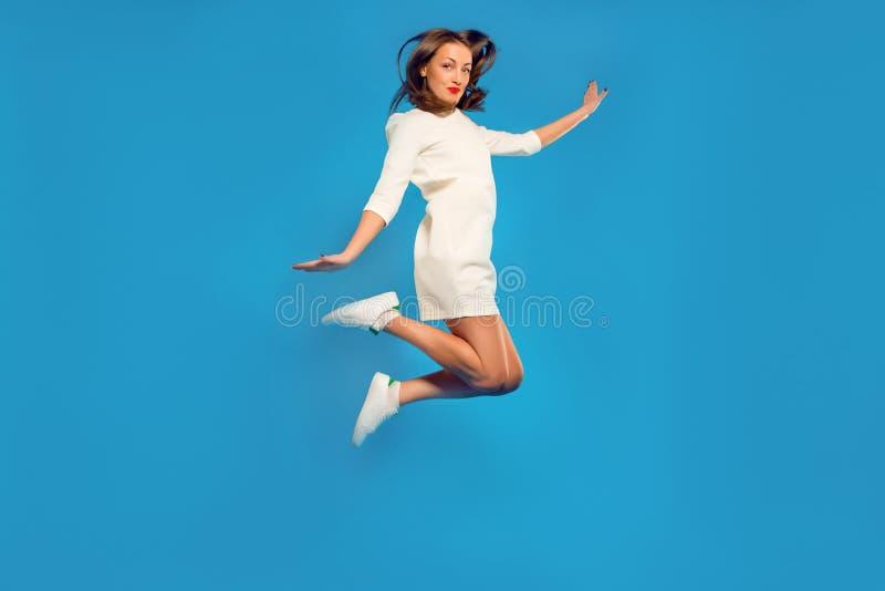 Rozochocona dziewczyna w białej sukni i sneakers pozuje w skoku zdjęcia royalty free