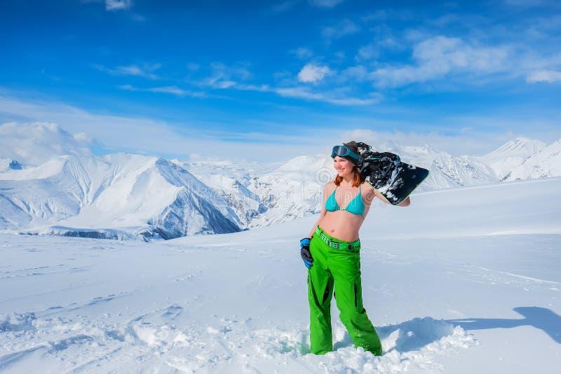 Rozochocona dziewczyna w swimsuit trzyma snowboard deskę na jej shoul fotografia stock