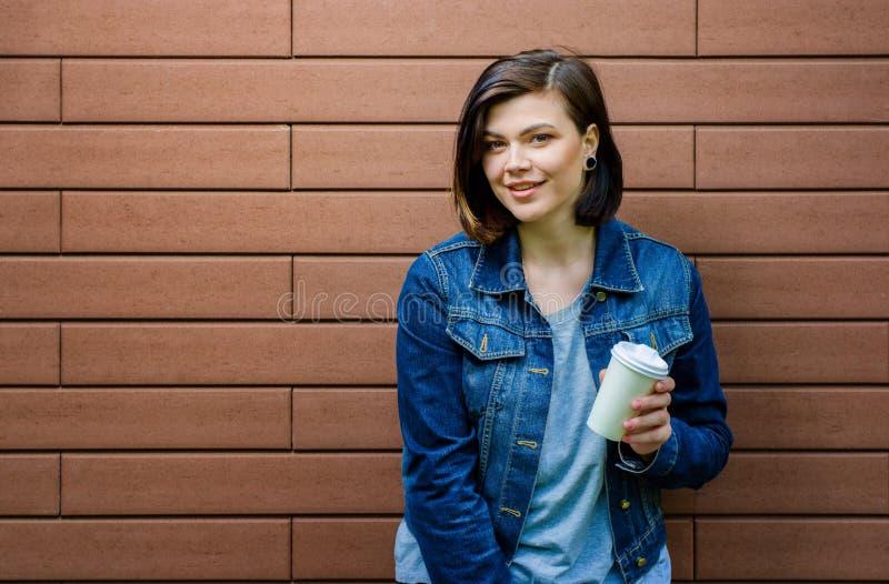 Rozochocona dziewczyna z filiżanką kawy blisko ściana z cegieł zdjęcie royalty free