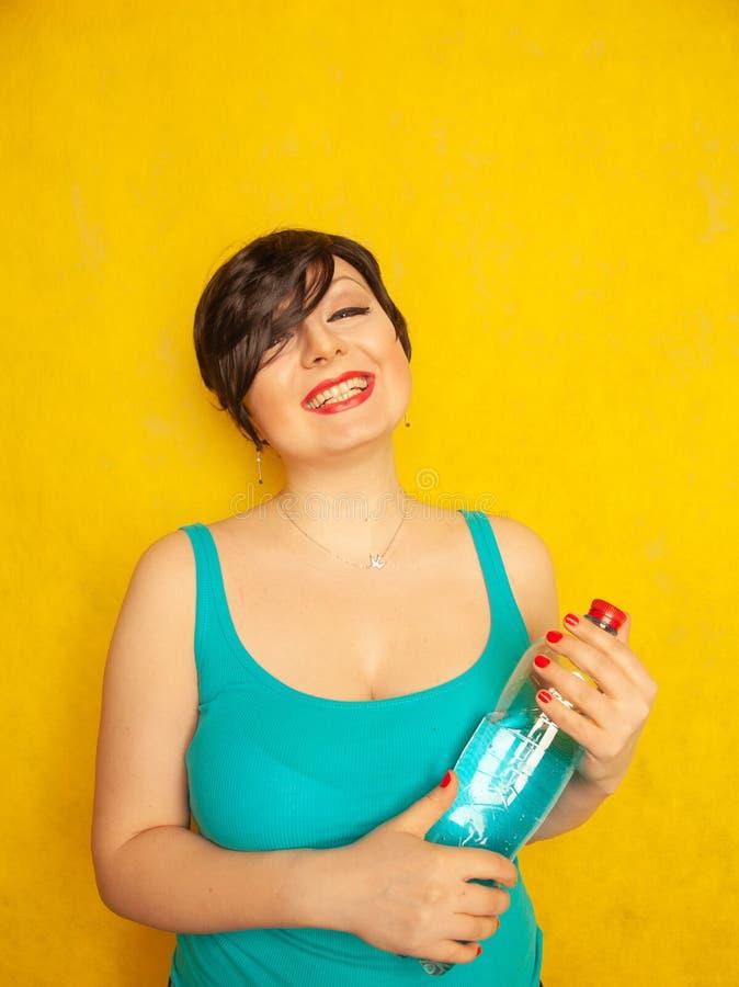 Rozochocona dziewczyna z krótkim włosy z dużą butelką woda na żółtym tle w studiu zdjęcie royalty free