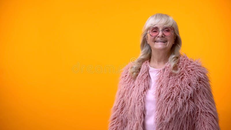 Rozochocona emeryt dama w śmiesznych menchii round i żakieta okularach przeciwsłonecznych pozuje na kamerze zdjęcia stock