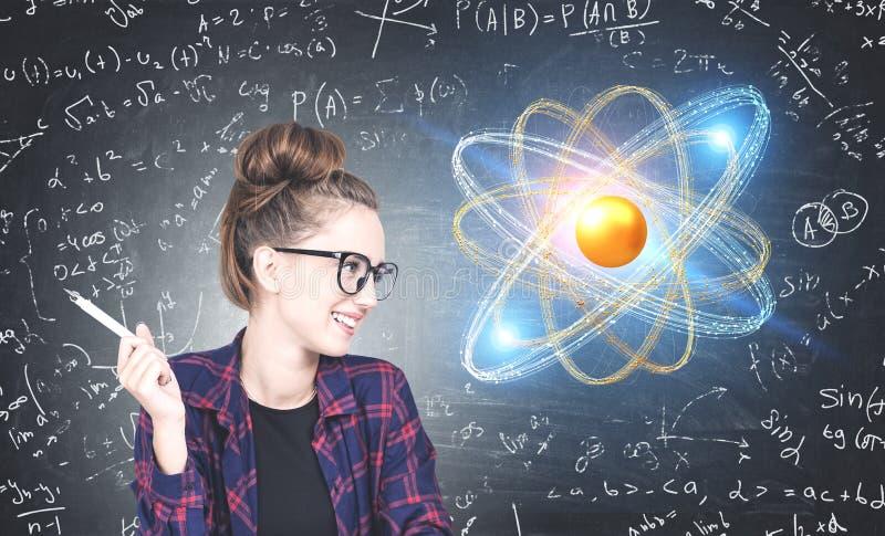 Rozochocona fajtłapy dziewczyna patrzeje atomu modela hologram obrazy royalty free