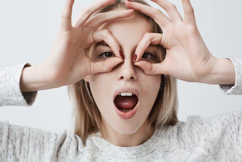 Rozochocona figlarnie młoda kobieta z blondynka włosy pokazuje Ok gestykuluje z oba rękami, udaje być ubranym widowiska zdjęcie stock
