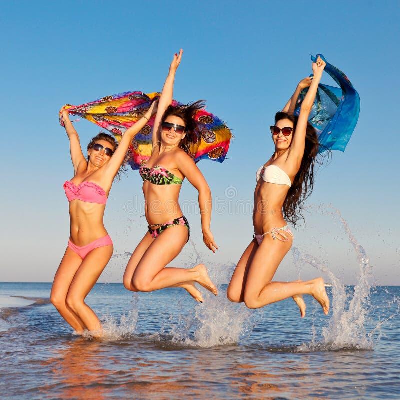 Rozochocona firma dziewczyny skacze w morzu obrazy royalty free