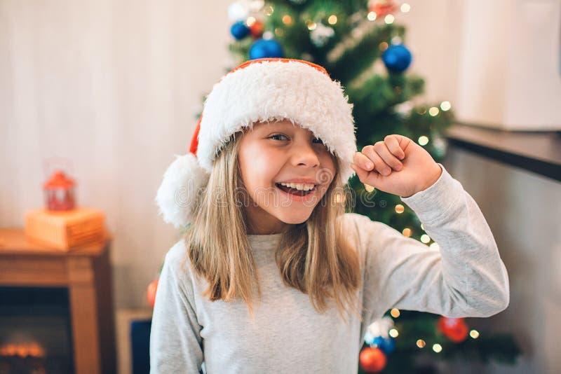 Rozochocona i pozytywna dziewczyna uśmiechnięta i roześmiana Trzyma krawędź jej Bożenarodzeniowy kapelusz Dziewczyna stojaki w po obraz royalty free