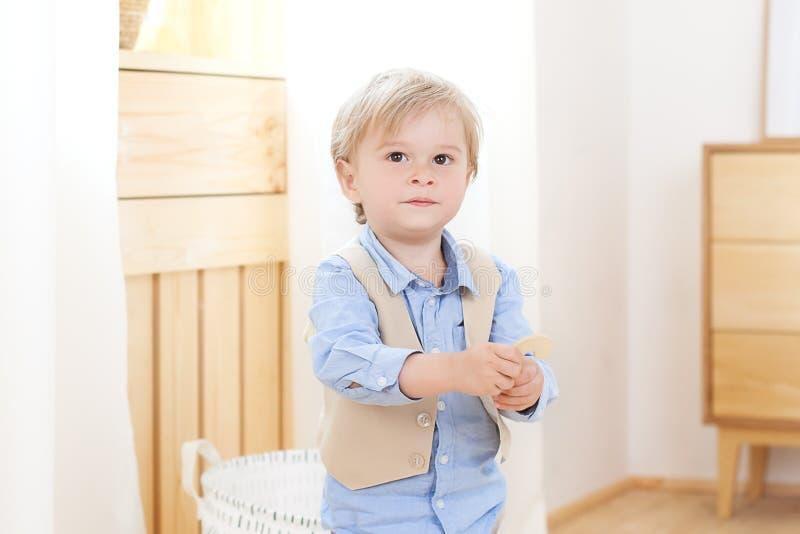 Rozochocona i uśmiechnięta chłopiec trzyma postać w jego rękach Dziecko w dziecinu Portret modny m?ski dziecko Uśmiechnięty chłop obraz stock