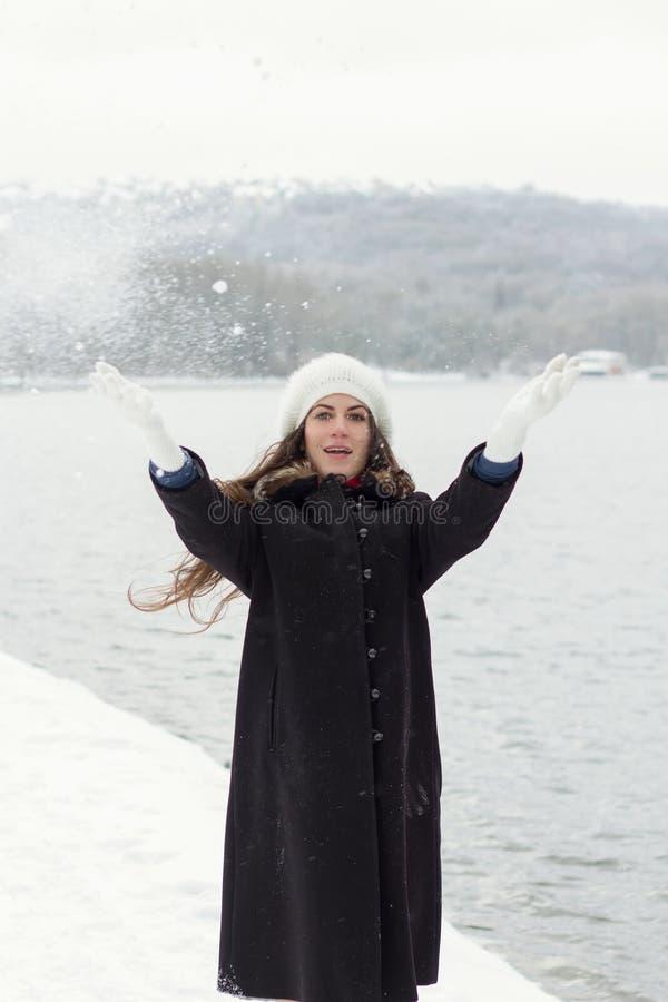 Rozochocona Kaukaska młoda kobieta w Śnieżnej pogodzie rzuca snowbal obrazy stock
