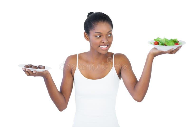 Rozochocona kobieta decyduje jeść healthily lub nie zdjęcia royalty free