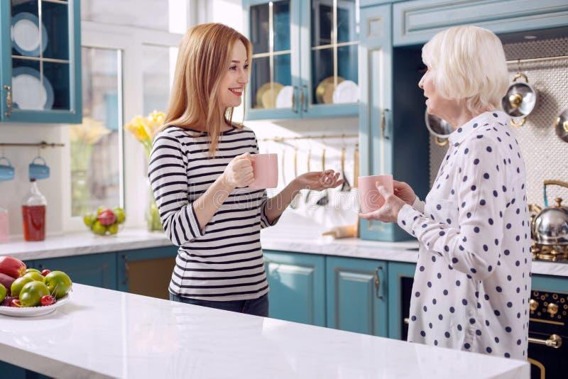 Rozochocona kobieta opowiada jej matka podczas gdy pijący kawę zdjęcia stock