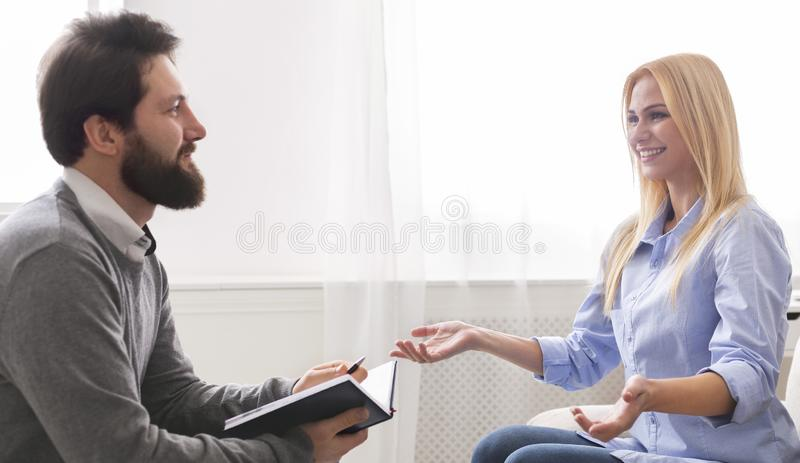 Rozochocona kobieta opowiada jej terapeuta przy biurem zdjęcie royalty free