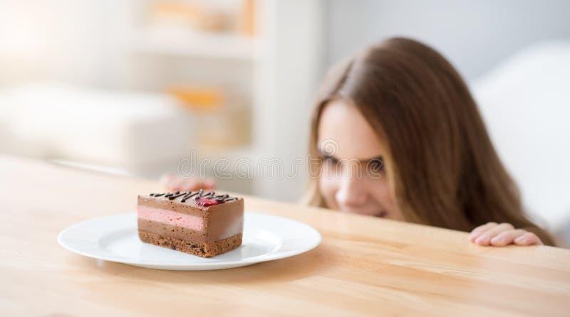 Rozochocona kobieta patrzeje kawałek tort zdjęcia royalty free