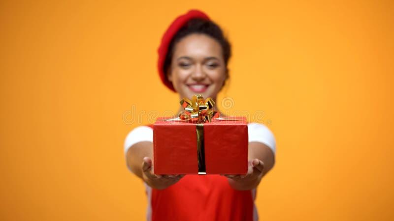 Rozochocona kobieta pokazuje czerwone prezenta pudełka ręki, wakacje teraźniejszy, rocznicowa niespodzianka fotografia stock