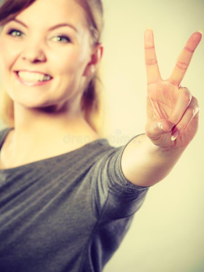Rozochocona kobieta pokazuje zwycięstwo symbol obrazy stock