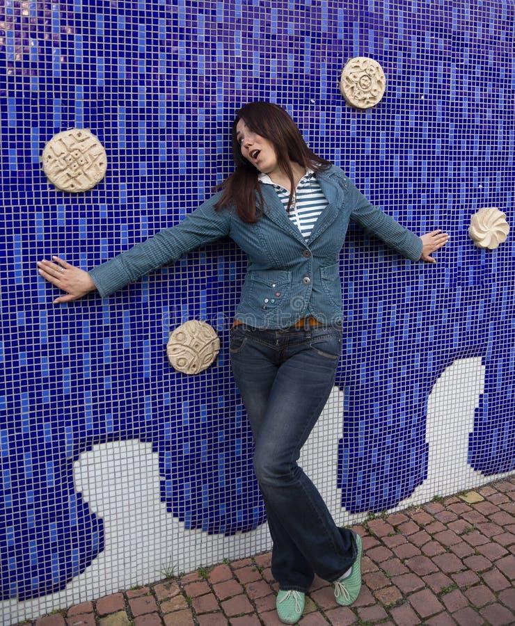 Rozochocona kobieta pozuje przeciw barwionej ścianie obraz royalty free