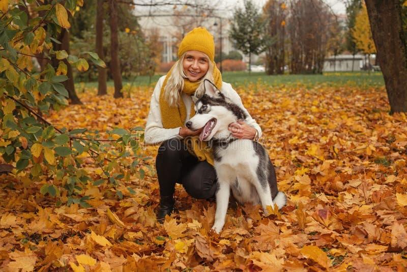 Rozochocona kobieta, psa mieć i odprowadzenie łuskowata zabawa plenerowa i obraz royalty free