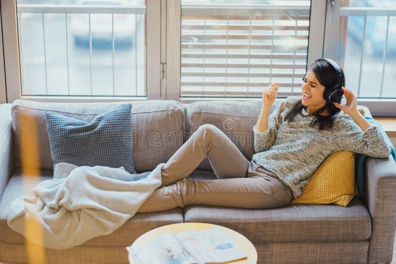 Rozochocona kobieta słucha muzyka z wielkimi hełmofonami i śpiewem Cieszący się słuchać w domu muzyka w czasie wolnym Relaksować  fotografia stock
