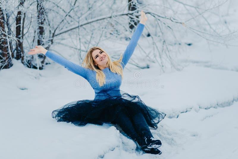 Rozochocona kobieta siedzi w śnieżnej zimie zdjęcia royalty free