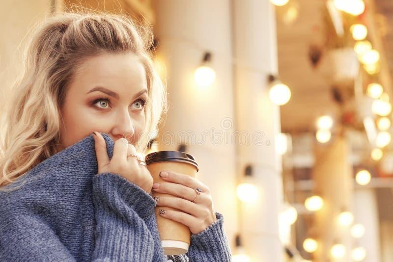 Rozochocona kobieta w ulicznej pije ranek kawie w światła słonecznego świetle zdjęcia royalty free