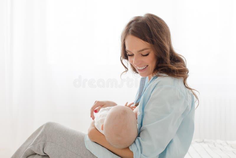 Rozochocona kobieta z dziecko piersią - karmiący zdjęcia royalty free