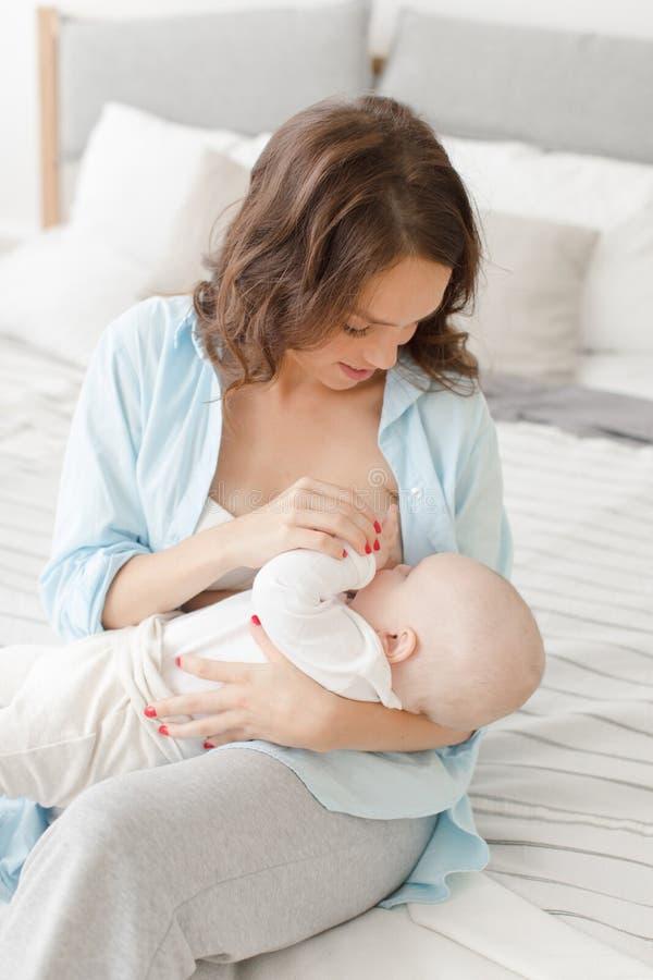 Rozochocona kobieta z dziecko piersią - karmiący zdjęcie royalty free