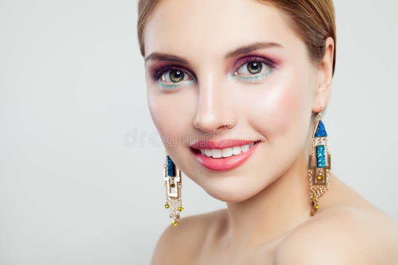 Rozochocona kobieta z makeup i złoto kolczykami, śliczny żeński twarzy zbliżenia portret fotografia royalty free