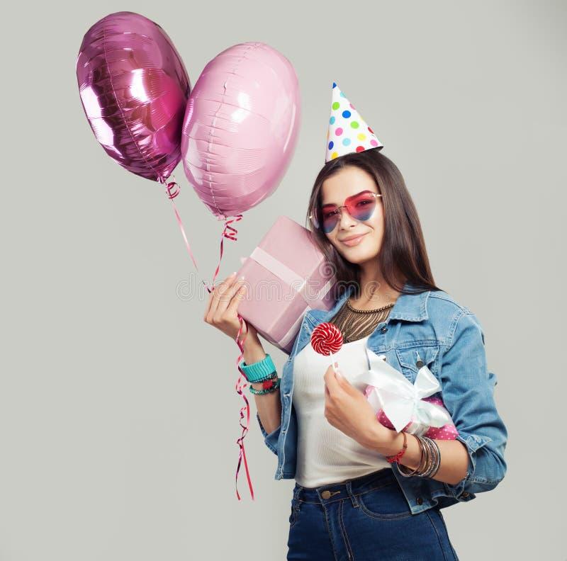 Rozochocona kobieta z prezenta pudełkiem, cukierku lizak, urodzinowa nakrętka obrazy stock