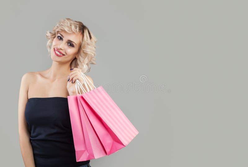 Rozochocona kobieta z torbami na zakupy, portret Piękny model z makeup i krótkim ostrzyżeniem fotografia stock