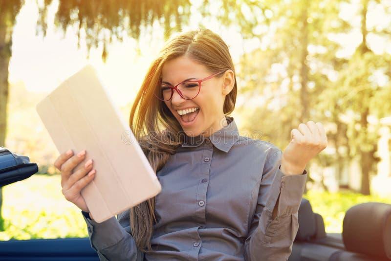 Rozochocona kobiety pozycja jej nową samochodową gmeranie pracą z ochraniacza komputerem w miastowym lato parku obrazy royalty free