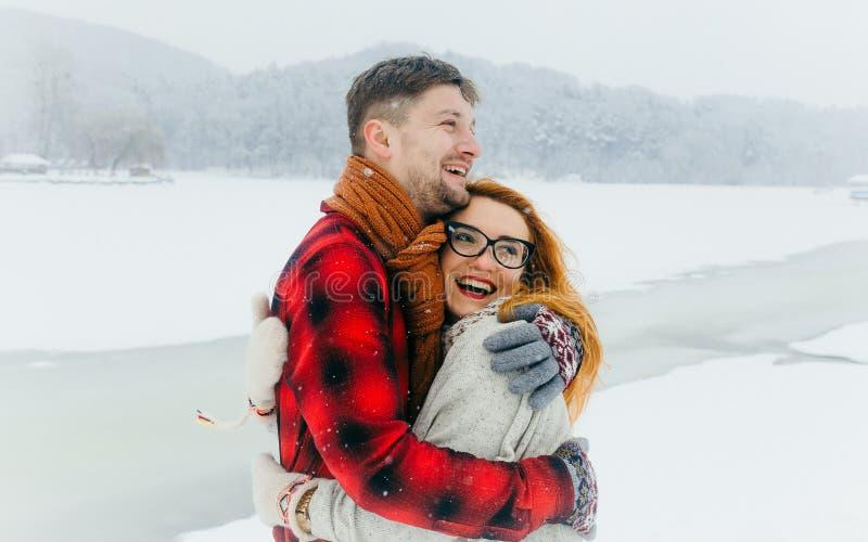 Rozochocona kochająca para jest roześmiana i przytulenie podczas opadu śniegu w śnieżnej łące Piękna czerwieni głowy dziewczyna z fotografia stock