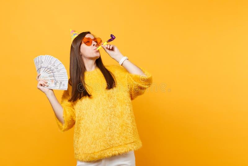 Rozochocona młoda kobieta w pomarańczowych kierowych szkłach, urodzinowy kapelusz z bawić się fajczanych mienie plika udziały dol zdjęcia stock