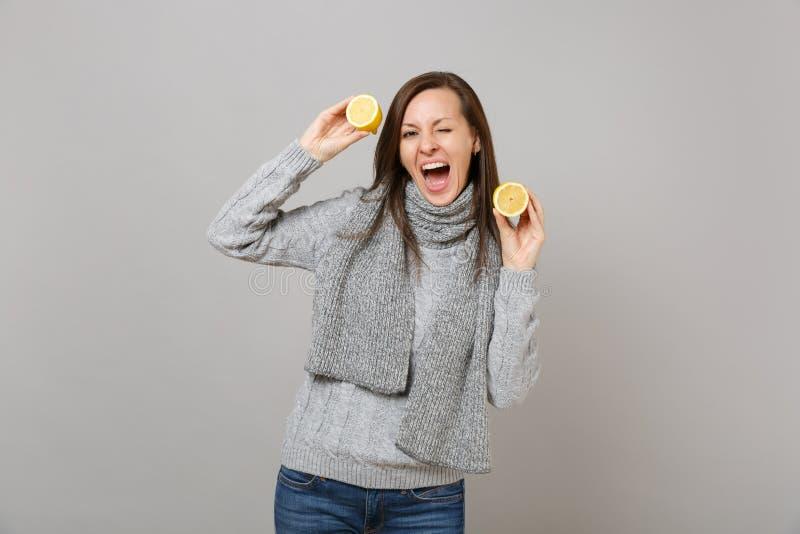 Rozochocona młoda kobieta w szarym pulowerze, szalika mruganie, mienie cytryny odizolowywać na popielatym tle w studiu Zdrowy obraz royalty free