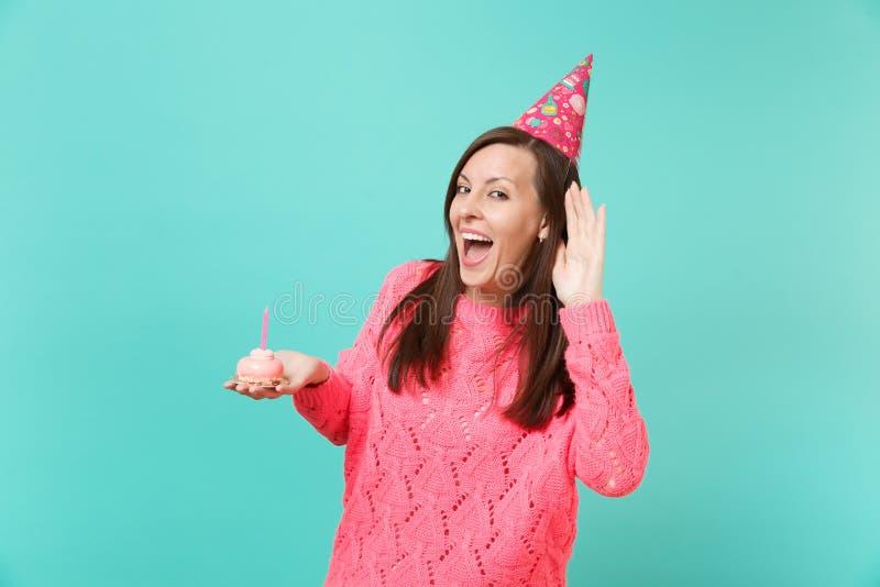 Rozochocona młoda kobieta w trykotowym różowym pulowerze, urodzinowy kapelusz podsłuchuje, słuchający gesta mienia w ręka torcie  zdjęcia royalty free
