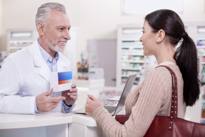 Rozochocona męska farmaceuta radzi klienta zdjęcia royalty free
