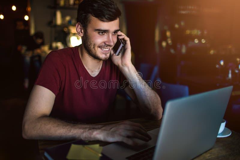 Rozochocona męska gmeranie praca w internecie przez netbook i telefonowaniu przez telefonu komórkowego fotografia stock