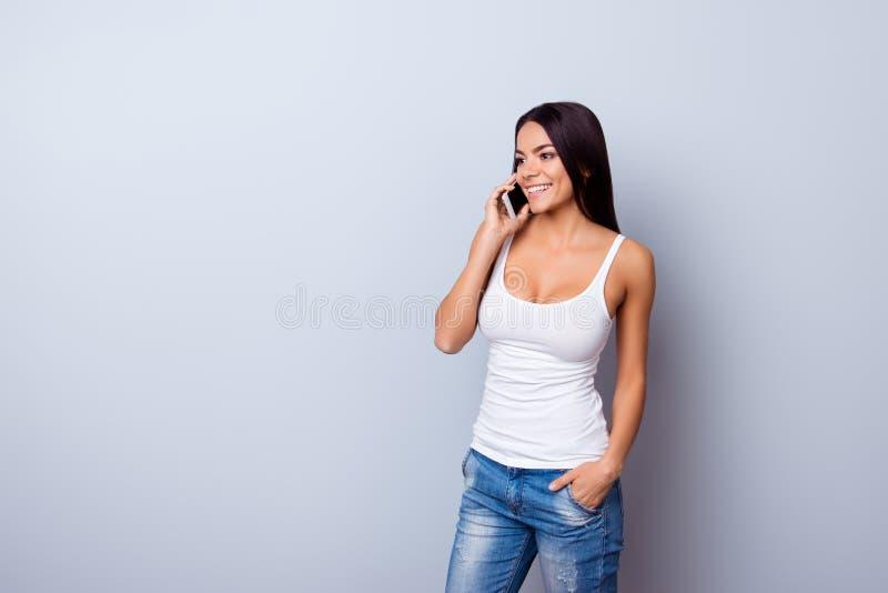 Rozochocona młoda śliczna łacińska dziewczyna opowiada na jej smili i telefonie fotografia royalty free