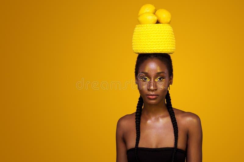Rozochocona młoda afrykańska kobieta z żółtym makeup na ona oczy Kobieta model przeciw żółtemu tłu z żółtymi cytrynami zdjęcia stock