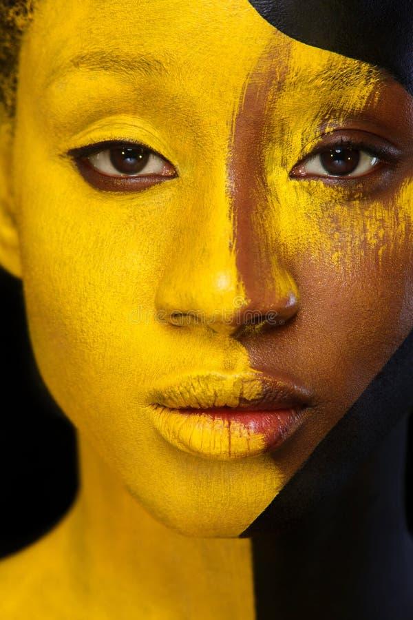 Rozochocona młoda afrykańska kobieta z sztuki mody makeup Zadziwiająca kobieta z czernią i żółtym farby makeup obraz royalty free