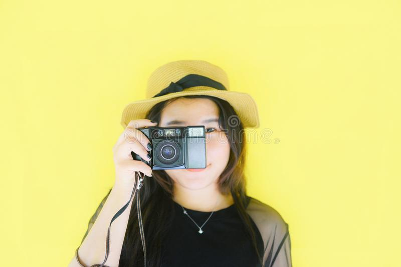 Rozochocona młoda Azjatycka kobieta portreta moda ono uśmiecha się i bierze obrazka fotografa z rocznika filmu kamerą na żółtym t zdjęcie stock