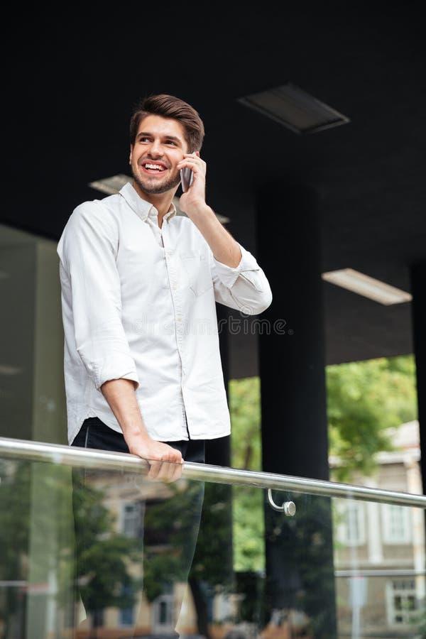 Rozochocona młoda biznesmen pozycja i opowiadać na telefonie komórkowym fotografia royalty free