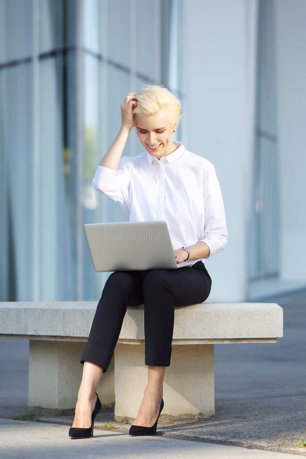 Rozochocona młoda biznesowa kobieta używa laptop outside obraz stock