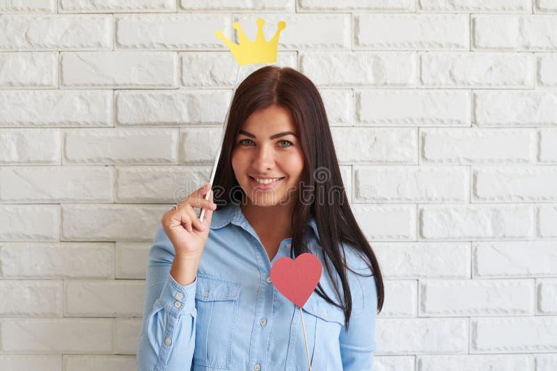 Rozochocona młoda brunetka pozuje podczas gdy trzymający papierową koronę obrazy stock