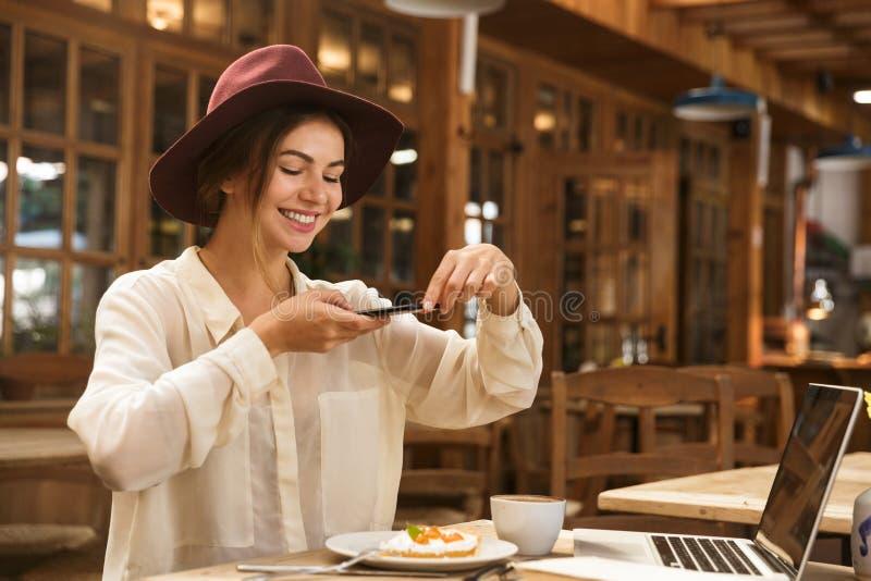 Rozochocona młoda kobieta bierze obrazek jej lunch obrazy stock
